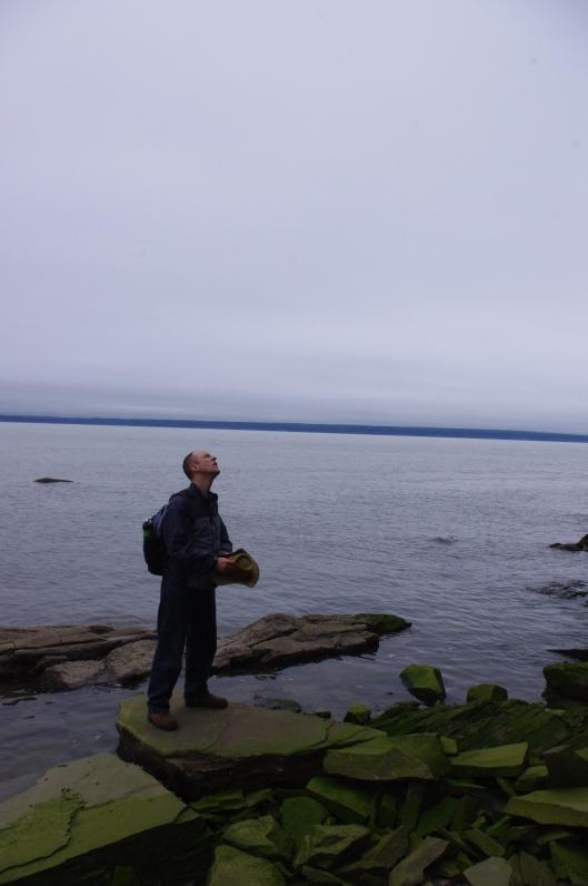 Adam examines the cliff faces at Cape Enrage