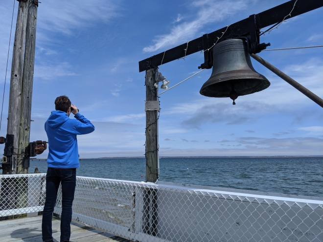Boy looking with binoculars under nautical bell with blue skies