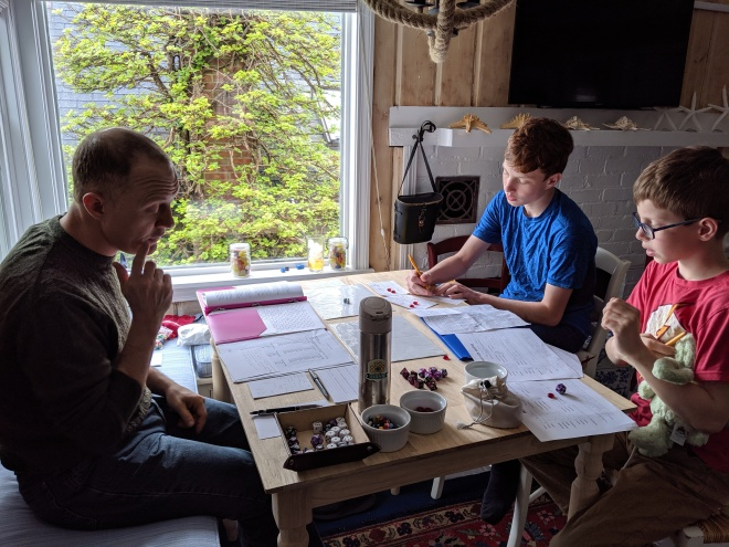 Two boys and their dad playing roleplaying games at a small table
