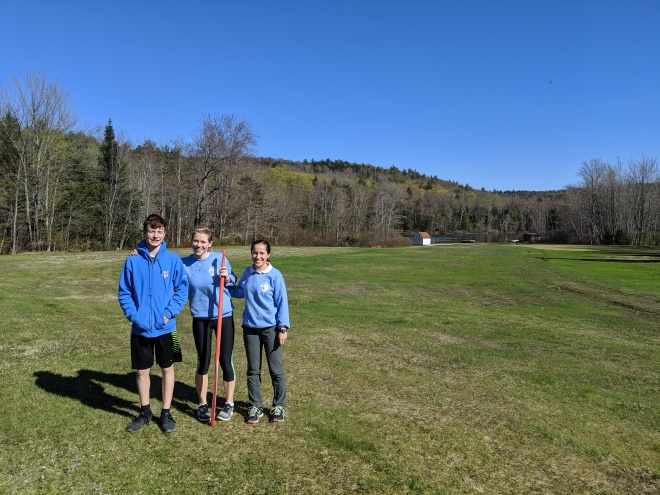 Three people standing on the WIlmot field in bright sunlight
